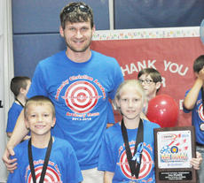 "<div class=""source"">Bobby Brockman</div><div class=""image-desc"">Kentucky Christian Academy archery coach Jason Keltner poses with the local school's top two finishers — Charles Cox, left, placed 15th while Briana Mardis, finished second — who guided them to the NASP elementary division national championship on Saturday in Louisville.</div><div class=""buy-pic""><a href=""/photo_select/51981"">Buy this photo</a></div>"