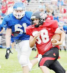"""<div class=""""source"""">Bobby Brockman</div><div class=""""image-desc"""">Taylor County High School junior Jarrett Benningfield (38) sweeps left around Adair County's Daniel Grant (61) during football scrimmage action on Friday night at Thomas Porter Stadium. The Cardinals open regular-season play on Saturday (8:30) vs. Russell County in the Forcht Bank Bowl at Campbellsville University while the Indians begin their slate on Friday, Aug. 30 at Caverna. Campbellsville kicks off this Friday (8:30) at CU vs. Edmonson County in the opening night of the Forcht Bank Bowl.  </div><div class=""""buy-pic""""><a href=""""/photo_select/46621"""">Buy this photo</a></div>"""