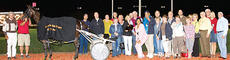"""<div class=""""source"""">Nigel Soult</div><div class=""""image-desc"""">Max and Ruth Ann Heath (behind end of race bike) were joined by VIP Internet Stable owners in the winner's circle. Pat and  Randall Phillips are visible in yellow fourth and fifth from right.</div><div class=""""buy-pic""""></div>"""