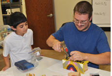 """<div class=""""source"""">Leslie Moore</div><div class=""""image-desc"""">Hassan Alabusalim watches Jordan Stapp, 4-H program assistant, build a birdhouse using wood and a soda can.</div><div class=""""buy-pic""""><a href=""""/photo_select/45136"""">Buy this photo</a></div>"""