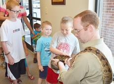 """<div class=""""source"""">Calen McKinney</div><div class=""""image-desc"""">Children line up to pet the snake that wrapped itself around Opferman.</div><div class=""""buy-pic""""><a href=""""/photo_select/45410"""">Buy this photo</a></div>"""