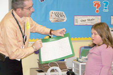 """<div class=""""source""""></div><div class=""""image-desc"""">Kylie Brown explains to Jr. Achievement volunteer Tim Buckner the different zones located within the classroom setting.</div><div class=""""buy-pic""""></div>"""