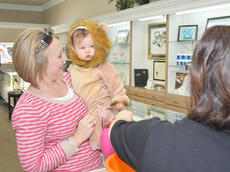 """<div class=""""source"""">Calen McKinney</div><div class=""""image-desc"""">A lion trick-or-treater isn't so sure about getting candy at Tucker Diamonds and Gold.</div><div class=""""buy-pic""""><a href=""""/photo_select/41078"""">Buy this photo</a></div>"""