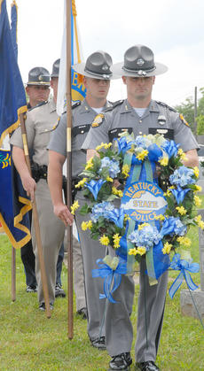 """<div class=""""source"""">Calen McKinney</div><div class=""""image-desc"""">KSP color guard members, led by Trooper Justin Phillips, march to place flowers on Johnny Edrington's grave.</div><div class=""""buy-pic""""><a href=""""/photo_select/37723"""">Buy this photo</a></div>"""