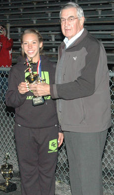 """<div class=""""source"""">Leonard VanMeter</div><div class=""""image-desc"""">Green County sophomore Erin Jaggers captured the prestigious girls' Ewing Award as the top point producers at the Heartland Athletic Conference Track Meet at Taylor County High School. Presenting Erin her award, at left, is Campbellsville physician Dr. James Ewing, whose father started the award some 50 years ago at the SKAC Track Meet. Erin placed first in the long and triple jumps and was on the victorious 4x200-meter relay team while finishing second in the 100-meter dash.</div><div class=""""buy-pic""""></div>"""