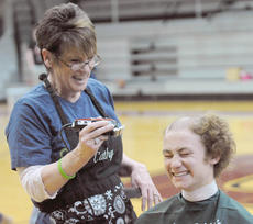 "<div class=""source"">Richard RoBards</div><div class=""image-desc"">Joey Hartlage smiles as he is shaved by Cathy Parish.</div><div class=""buy-pic""></div>"