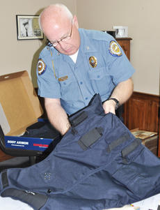 "<div class=""source"">Leslie Moore</div><div class=""image-desc"">Campbellsville Police Chief Tim Hazlette inserts the interior panels into an outside-wear body armor carrier.</div><div class=""buy-pic""><a href=""/photo_select/44850"">Buy this photo</a></div>"
