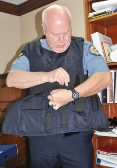 "<div class=""source"">Leslie Moore</div><div class=""image-desc"">Campbellsville Police Chief Tim Hazlette puts on outside-wear body armor used to protect officers.</div><div class=""buy-pic""><a href=""/photo_select/44851"">Buy this photo</a></div>"