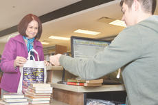 """<div class=""""source"""">Calen McKinney</div><div class=""""image-desc"""">LaVerne Reliford of Columbia, a long-time Taylor County Public Library patron, checks out books last Wednesday with Circulation Clerk Wes Phillips. The new library officially opened its doors to the public last Wednesday.</div><div class=""""buy-pic""""><a href=""""/photo_select/43331"""">Buy this photo</a></div>"""