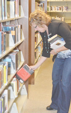 """<div class=""""source"""">Calen McKinney</div><div class=""""image-desc"""">Debbie Parson, adult services librarian, shelves books last Wednesday, official opening day for the new Taylor County Public Library.</div><div class=""""buy-pic""""><a href=""""/photo_select/43334"""">Buy this photo</a></div>"""
