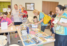 """<div class=""""source"""">Calen McKinney</div><div class=""""image-desc"""">Participants who signed up for the summer reading program were given a free book.</div><div class=""""buy-pic""""><a href=""""/photo_select/45244"""">Buy this photo</a></div>"""