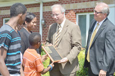"""<div class=""""source"""">Calen McKinney</div><div class=""""image-desc"""">Campbellsville University President Dr. Michael Carter, center, presents a plaque to Frances Clinkscales' family members after a courtyard was dedicated in her honor. Campbellsville Mayor Tony Young, who worked with CU to build the courtyard, is at right.</div><div class=""""buy-pic""""><a href=""""/photo_select/40111"""">Buy this photo</a></div>"""