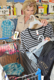 "<div class=""source"">Calen McKinney</div><div class=""image-desc"">Court security officer Lisa Bagby totals the cost of a young girl's new clothing.</div><div class=""buy-pic""><a href=""/photo_select/46287"">Buy this photo</a></div>"