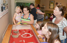"""<div class=""""source"""">Calen McKinney</div><div class=""""image-desc"""">Children and adults alike look at a display of fossils at the visitor's center.</div><div class=""""buy-pic""""><a href=""""/photo_select/45262"""">Buy this photo</a></div>"""
