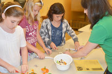 """<div class=""""source"""">Calen McKinney</div><div class=""""image-desc"""">Amanda Sublett, Taylor County Extension agent for 4-H/Youth Development, at right, helps, from left, Rachel Cowherd, Olivia Herron and Mercedes Clifton learn the proper way to cut vegetables.</div><div class=""""buy-pic""""><a href=""""http://web2.lcni5.com/cgi-bin/c2newbuyphoto.cgi?pub=085&orig=chef_day_camp_1.jpg"""" target=""""_new"""">Buy this photo</a></div>"""