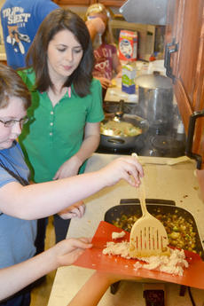 """<div class=""""source"""">Calen McKinney</div><div class=""""image-desc"""">Amanda Sublett, Taylor County Extension agent for 4-H/Youth Development, watches as Cade Malone and Colleen Spencer, hidden, add chicken to their stir-fry as it cooks.</div><div class=""""buy-pic""""><a href=""""http://web2.lcni5.com/cgi-bin/c2newbuyphoto.cgi?pub=085&orig=chef_day_camp_10.jpg"""" target=""""_new"""">Buy this photo</a></div>"""