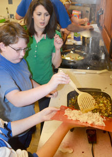"""<div class=""""source"""">Calen McKinney</div><div class=""""image-desc"""">Amanda Sublett, Taylor County Extension agent for 4-H/Youth Development, watches as Cade Malone and Colleen Spencer, hidden, add chicken to their stir-fry as it cooks.</div><div class=""""buy-pic""""><a href=""""http://web2.lcni5.com/cgi-bin/c2newbuyphoto.cgi?pub=085&orig=chef_day_camp_11.jpg"""" target=""""_new"""">Buy this photo</a></div>"""