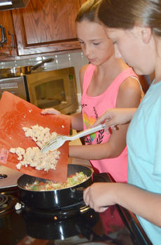 """<div class=""""source"""">Calen McKinney</div><div class=""""image-desc"""">McKenzie Clark, at left, and Grace Malone add chicken to their stir-fry as it cooks.</div><div class=""""buy-pic""""><a href=""""http://web2.lcni5.com/cgi-bin/c2newbuyphoto.cgi?pub=085&orig=chef_day_camp_12.jpg"""" target=""""_new"""">Buy this photo</a></div>"""