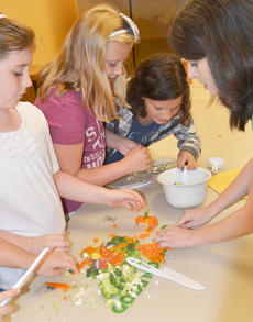 """<div class=""""source"""">Calen McKinney</div><div class=""""image-desc"""">Amanda Sublett, Taylor County Extension agent for 4-H/Youth Development, helps, from left, Rachel Cowherd, Olivia Herron and Mercedes Clifton know the proper technique to cutting vegetables.</div><div class=""""buy-pic""""><a href=""""http://web2.lcni5.com/cgi-bin/c2newbuyphoto.cgi?pub=085&orig=chef_day_camp_18.jpg"""" target=""""_new"""">Buy this photo</a></div>"""