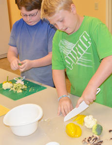 """<div class=""""source"""">Calen McKinney</div><div class=""""image-desc"""">Cade Malone, at left, and Levi Dicken chop vegetables for their stir-fry lunch.</div><div class=""""buy-pic""""><a href=""""http://web2.lcni5.com/cgi-bin/c2newbuyphoto.cgi?pub=085&orig=chef_day_camp_2.jpg"""" target=""""_new"""">Buy this photo</a></div>"""