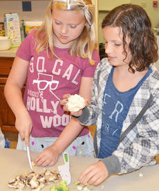"""<div class=""""source"""">Calen McKinney</div><div class=""""image-desc"""">Olivia Herron, at left, and Mercedes Clifton work to chop vegetables for their stir-fry lunch.</div><div class=""""buy-pic""""><a href=""""http://web2.lcni5.com/cgi-bin/c2newbuyphoto.cgi?pub=085&orig=chef_day_camp_4.jpg"""" target=""""_new"""">Buy this photo</a></div>"""