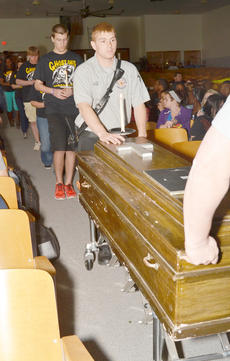 "<div class=""source"">Calen McKinney</div><div class=""image-desc"">James Abt pushes a casket in symbolizing the grim reaper's 12 victims at the Ghost Out ceremony at Campbellsville High School begins.</div><div class=""buy-pic""><a href=""/photo_select/51434"">Buy this photo</a></div>"