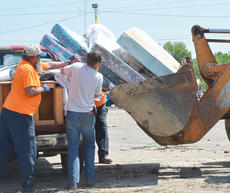 """<div class=""""source"""">Calen McKinney</div><div class=""""image-desc"""">County Road Department workers unload items from a truck.</div><div class=""""buy-pic""""><a href=""""http://web2.lcni5.com/cgi-bin/c2newbuyphoto.cgi?pub=085&orig=cleanup_2.jpg"""" target=""""_new"""">Buy this photo</a></div>"""