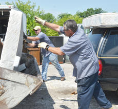 """<div class=""""source"""">Calen McKinney</div><div class=""""image-desc"""">City workers Mark Inman, at left, and Kenny Childers unload a mattress from a truck.</div><div class=""""buy-pic""""><a href=""""http://web2.lcni5.com/cgi-bin/c2newbuyphoto.cgi?pub=085&orig=cleanup_4.jpg"""" target=""""_new"""">Buy this photo</a></div>"""