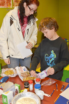 """<div class=""""source"""">Calen McKinney</div><div class=""""image-desc"""">Jennifer Heisler-Quinn helps her son, Zakk, put together ingredients to make soup. The Heisler-Quinn family is working at Amazon.com and is camping in Campbellsville.</div><div class=""""buy-pic""""><a href=""""/photo_select/49181"""">Buy this photo</a></div>"""