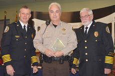 """<div class=""""source"""">Calen McKinney</div><div class=""""image-desc"""">Taylor County Sheriff's Deputy Dickie Benningfield receives a Distinguished Service Award from Campbellsville Fire & Rescue Chief Kyle Smith, at right, and Taylor County Fire & Rescue Chief George Wilson.</div><div class=""""buy-pic""""><a href=""""http://web2.lcni5.com/cgi-bin/c2newbuyphoto.cgi?pub=085&orig=fire_rescue_awards-benningfield_web.jpg"""" target=""""_new"""">Buy this photo</a></div>"""