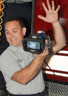 """<div class=""""source"""">Calen McKinney</div><div class=""""image-desc"""">Campbellsville Fire & Rescue Engineer Keith Bricken, shown her conducting a fire prevention program for local children, shows how a camera helps firefighters detect heat. Bricken received this year's Firefighter of the Year Award.</div><div class=""""buy-pic""""><a href=""""http://web2.lcni5.com/cgi-bin/c2newbuyphoto.cgi?pub=085&orig=fire_rescue_awards-bricken.jpg"""" target=""""_new"""">Buy this photo</a></div>"""