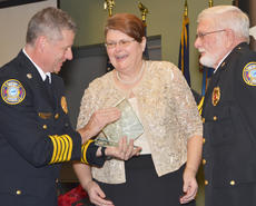 """<div class=""""source"""">Calen McKinney</div><div class=""""image-desc"""">Connie Wooley, administrative assistant at Campbellsville Fire & Rescue, receives this year's Jamia Skaggs Behind the Scenes Award from Campbellsville Fire & Rescue Chief Kyle Smith, at right, and Taylor County Fire & Rescue Chief George Wilson.</div><div class=""""buy-pic""""><a href=""""http://web2.lcni5.com/cgi-bin/c2newbuyphoto.cgi?pub=085&orig=fire_rescue_awards-wooley_0.jpg"""" target=""""_new"""">Buy this photo</a></div>"""
