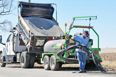"""<div class=""""source"""">Leslie Moore</div><div class=""""image-desc"""">Taylor County Road Department worker Harold Wethington uses the Total Patcher machine to fill a pothole on Blue Hole Road.</div><div class=""""buy-pic""""><a href=""""/photo_select/50556"""">Buy this photo</a></div>"""