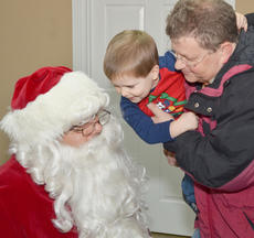 """<div class=""""source"""">Calen McKinney</div><div class=""""image-desc"""">Micah Goodwin isn't so sure about sitting in Santa's lap. But to be sure Santa knows what to bring him this year, Micah, held by his father, the Rev. Michael Goodwin, whispers what he wants in Santa's ear.</div><div class=""""buy-pic""""><a href=""""/photo_select/48960"""">Buy this photo</a></div>"""