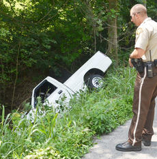 "<div class=""source"">Calen McKinney</div><div class=""image-desc"">Taylor County Sheriff's Deputy Branden Wilson writes information for a report about a crash involving this truck, which landed on its side in a ditch after the driver, Johnny T. Embry of Campbellsville, lost control.</div><div class=""buy-pic""><a href=""/photo_select/54751"">Buy this photo</a></div>"