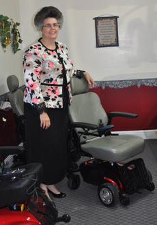 """<div class=""""source"""">Leslie Moore</div><div class=""""image-desc"""">Teresa Lynne Aldridge, owner of American Mobility Products, Inc., stands in front of a motorized wheelchair that she says can change the lives of those who need mobility assistance.</div><div class=""""buy-pic""""><a href=""""/photo_select/47770"""">Buy this photo</a></div>"""