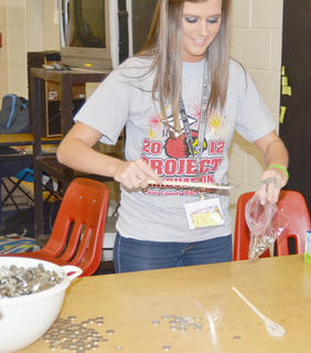Megan Skaggs tries to scoop up as many coins as possible with a cooking utensil.