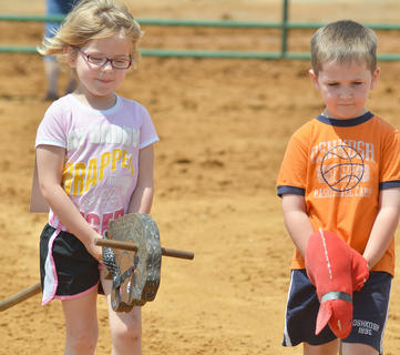 Bailey Stewart, at left, of Owenton, and Luke Adkinson of Campbellsville ride their stick horses in the stick horse class. They both won first place.