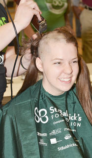 CU swim team member Bailey Foxworth shaves her head.