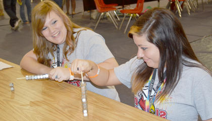 Melanie Moore, left, and Sara Murphy try their best at the Stack the Nuts game.