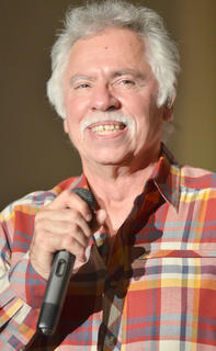 "Joe Bonsall smiles as the crowd sings along to ""A Christmas Love Song."""