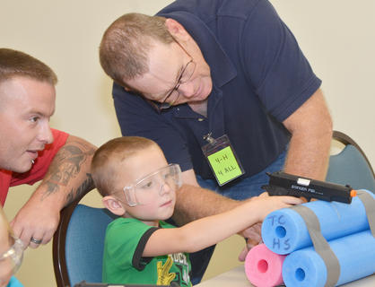 Landon Boots, 4, of Campbellsville, takes aim as he takes target practice with an airsoft pistol as his dad, Michael, at left, and Randy Wayne, at right, watch.