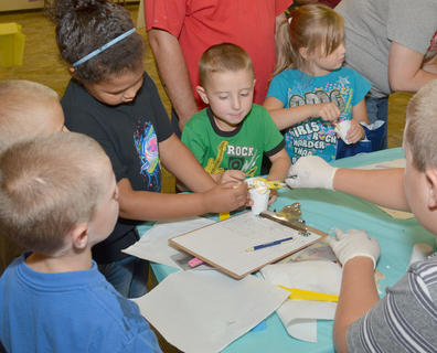 Local children learn how to make their own silly putty.