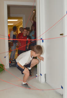 "Axel Dysholm, 6, of Campbellsville, carefully makes his way through the ""Mission Impossible""-style maze, complete with fog and red yarn to simulate lasers."