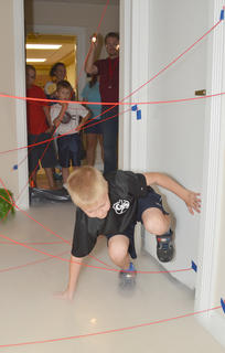 "Rhett Dysholm, 9, of Campbellsville, carefully makes his way through the ""Mission Impossible""-style maze, complete with fog and red yarn to simulate lasers."