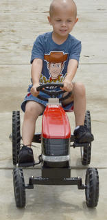 Michael Crews, 4, takes his turn riding a miniature tractor.