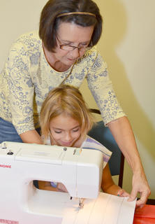 Ann Beard helps Brook Mays, 7, of Campbellsville, learn to sew.