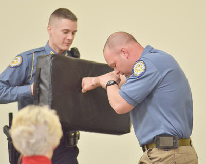 "Warren demonstrates, with Campbellsville Police Officer Roy Rodgers, how a person should punch an assailant. He said the goal during a fight is to only have to strike an attacker once, and hard enough to get him or her to stop the attack. ""Throw it with everything you've got,"" he said."