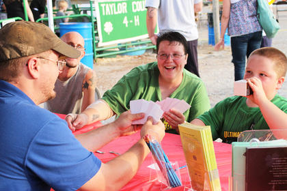 Taylor County 4H Assistant Jordan Stapp shows Jonathan Edwards, left, and Jennifer and Zackary Miller how to play the farm animal version of Spoons.