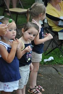 Alyssa Munn, 2, and Zoey (2) and Chloe Pelcher (4) watch the parade on Monday morning.